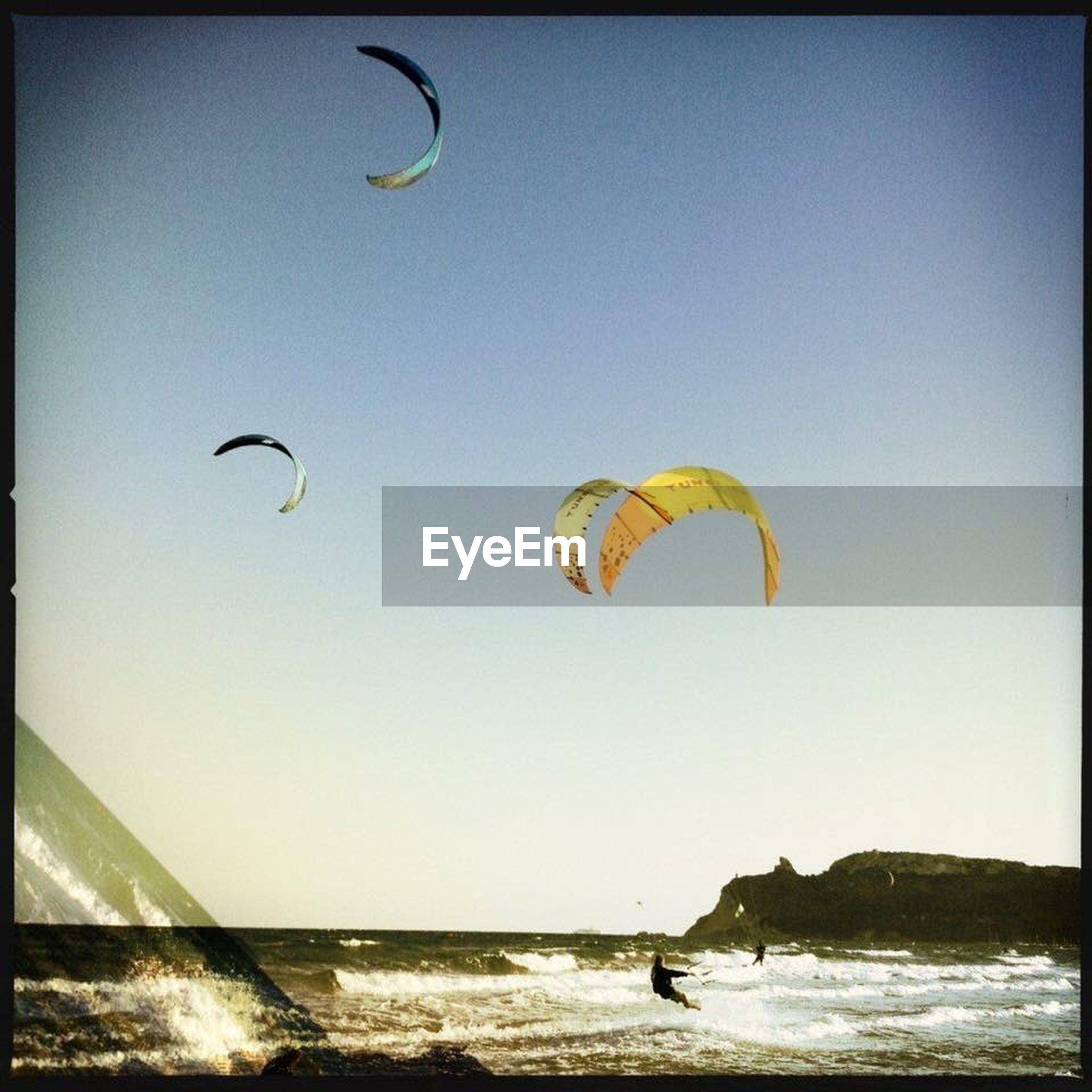 parachute, flying, mid-air, sea, clear sky, extreme sports, leisure activity, beach, paragliding, sport, copy space, adventure, lifestyles, horizon over water, vacations, fun, sand, water