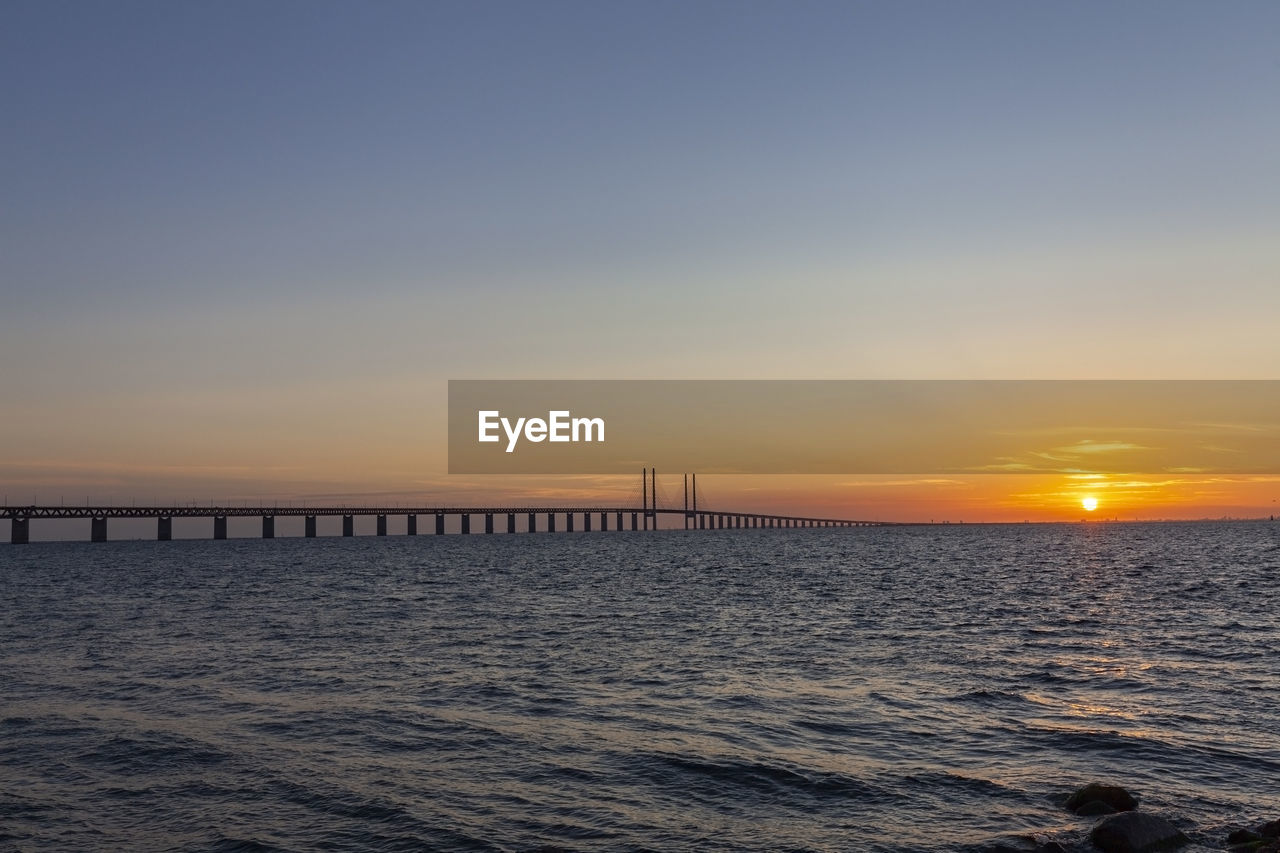 sky, sunset, water, sea, scenics - nature, beauty in nature, orange color, sun, tranquil scene, tranquility, horizon, idyllic, horizon over water, nature, waterfront, bridge, copy space, no people, built structure, bridge - man made structure, outdoors