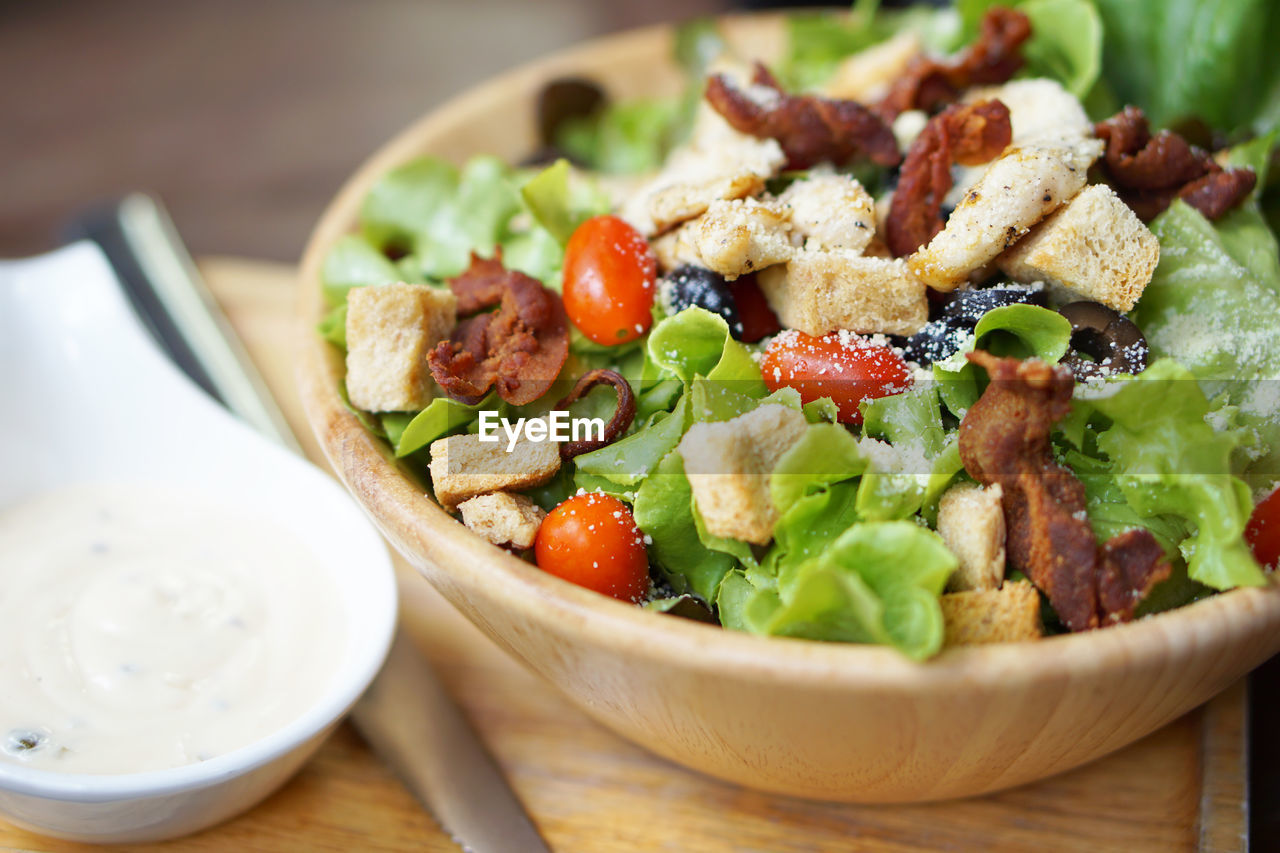 food, food and drink, healthy eating, freshness, vegetable, bowl, table, wellbeing, ready-to-eat, salad, indoors, close-up, still life, serving size, no people, eating utensil, spoon, fruit, wood - material, kitchen utensil, vegetarian food, greek food, crockery, setting