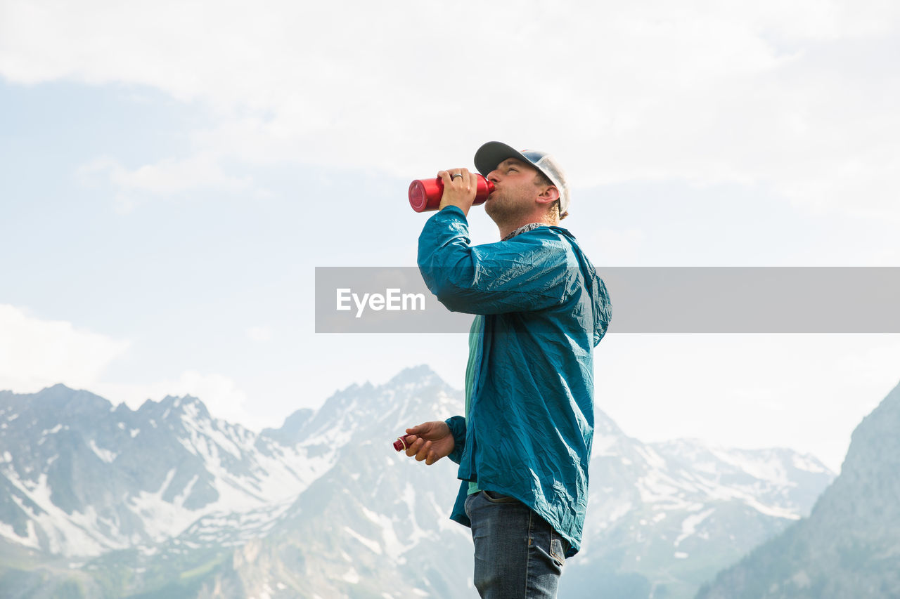 Man Drinking Water While Standing By Mountain Against Clear Sky
