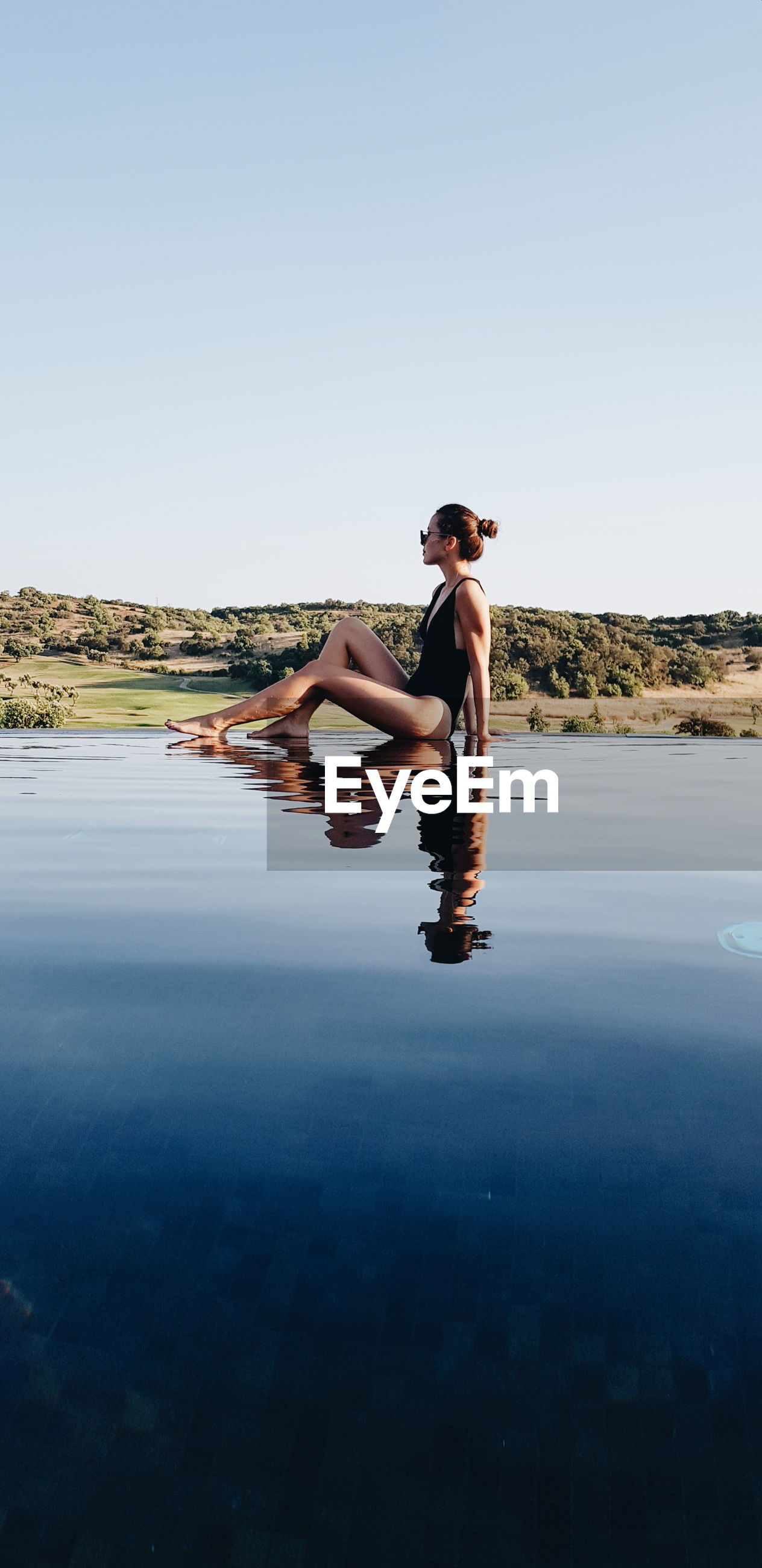 Full length of woman sitting in water against clear sky