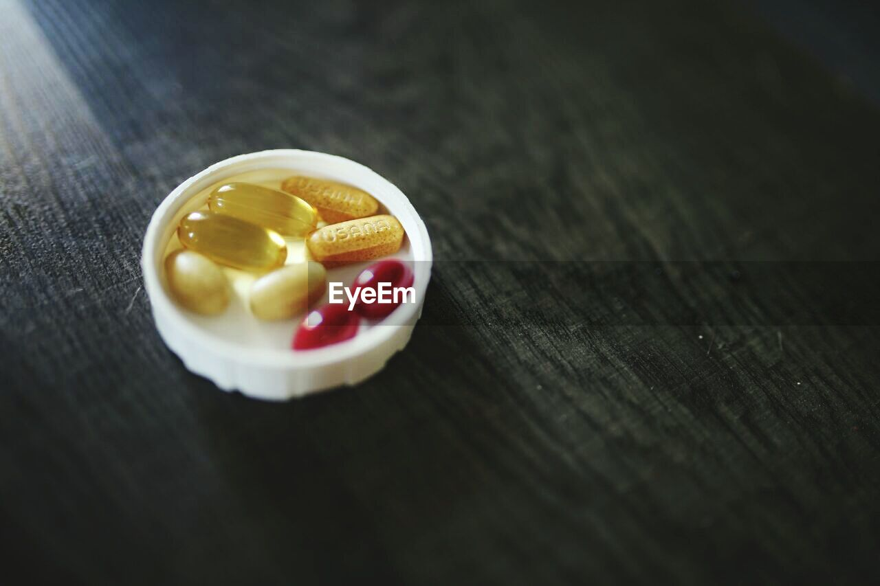 pill, table, dose, close-up, medicine, selective focus, no people, still life, healthcare and medicine, indoors, capsule, wood - material, high angle view, nutritional supplement, vitamin, single object, day, food, sweet food, temptation