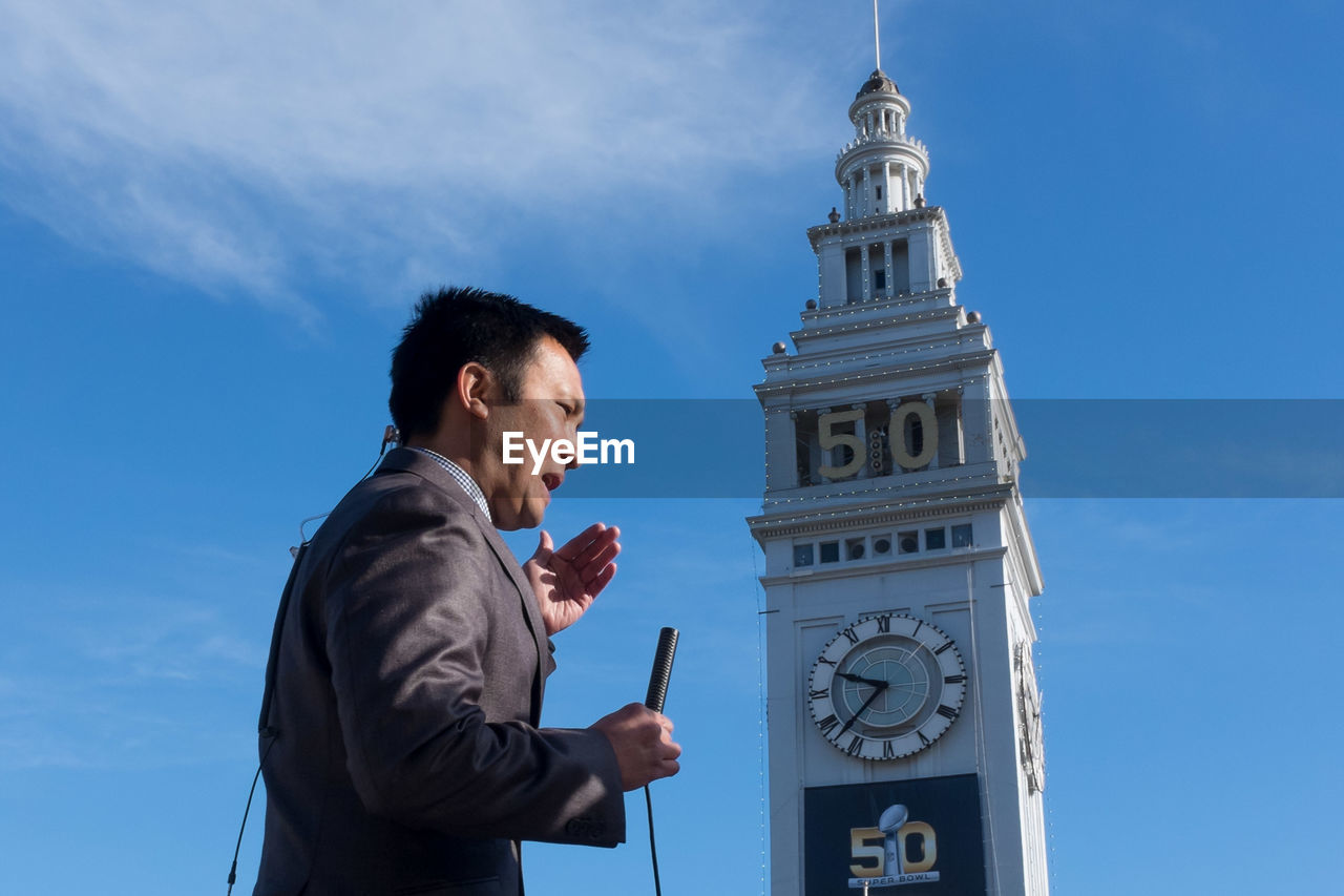 low angle view, architecture, sky, building exterior, cloud - sky, clock, built structure, time, clock tower, day, outdoors, one person, real people, businessman, men, well-dressed, lifestyles, standing, people