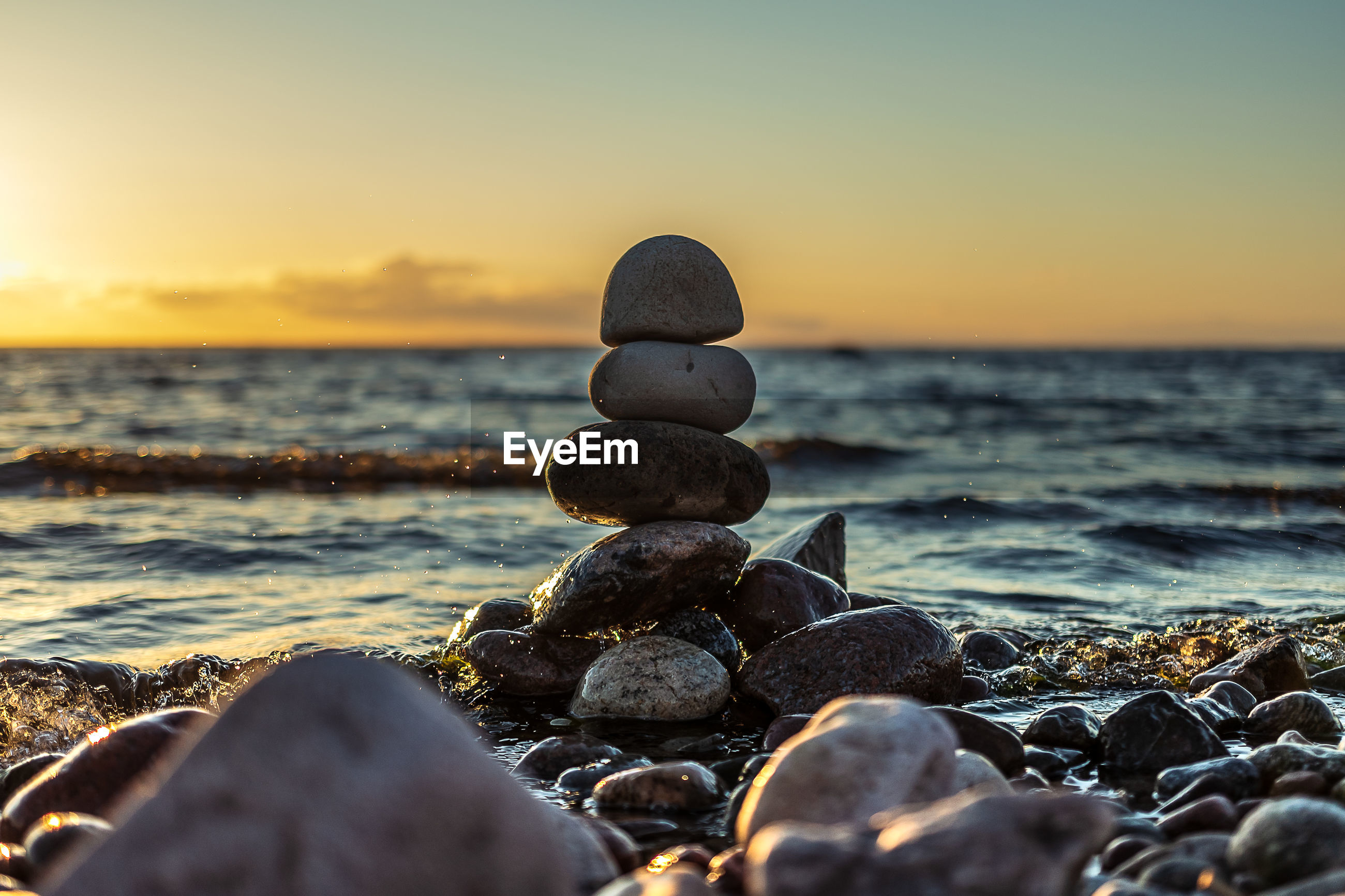 Sunset on a pebble beach where a stack of round stones stands on each other.