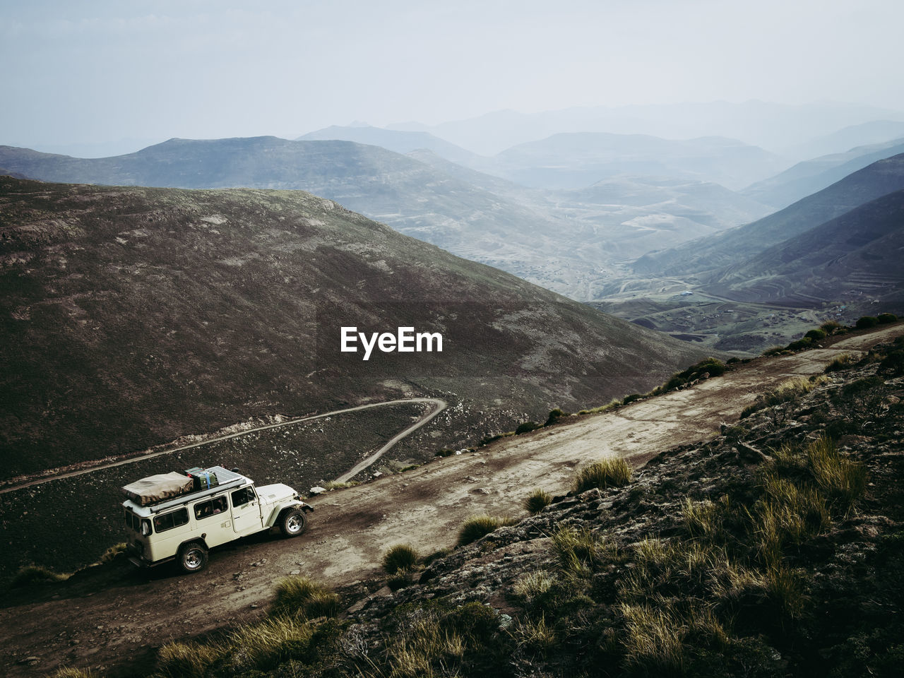 High Angle View Of Mountain Dirt Road And 4X4 Vehicle Amidst Dark Landscape Against Sky, Lesotho, Africa
