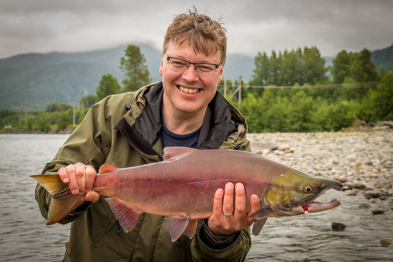 Portrait of smiling man holding fish standing by river