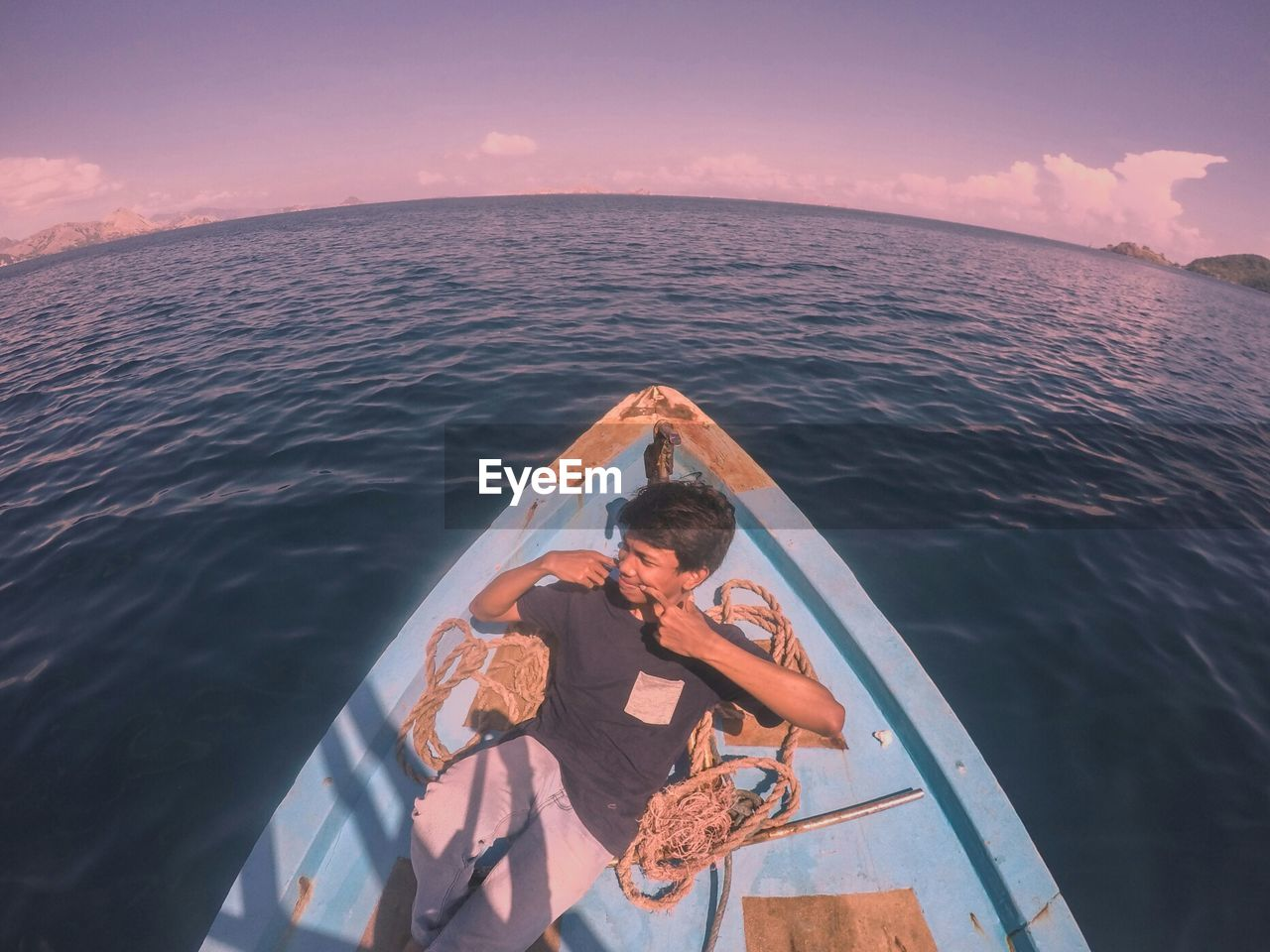 High angle view of young man looking away while sitting in boat on sea against sky during sunset