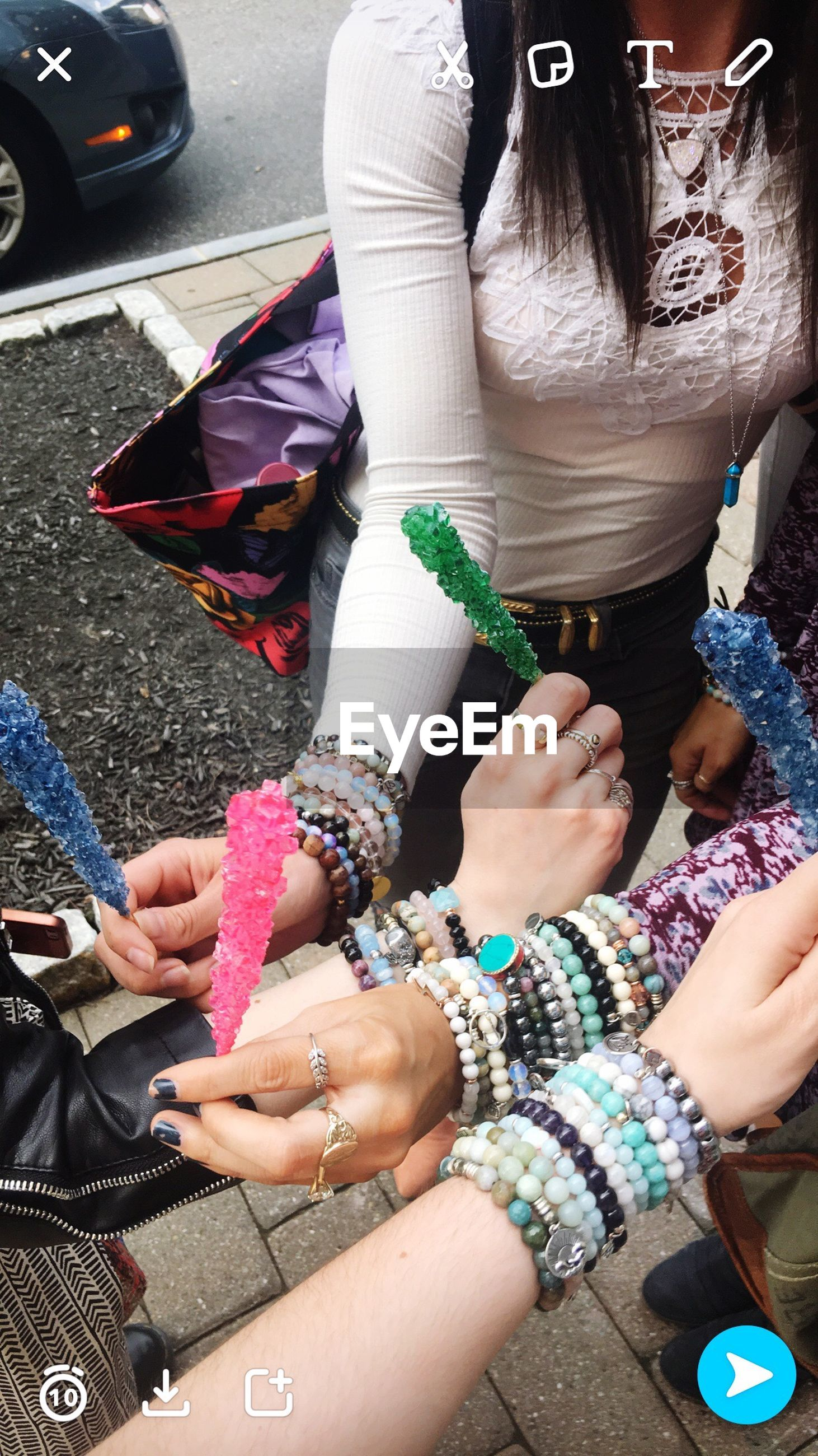 real people, human hand, bracelet, high angle view, holding, day, low section, women, outdoors, human body part, sitting, togetherness, nail polish