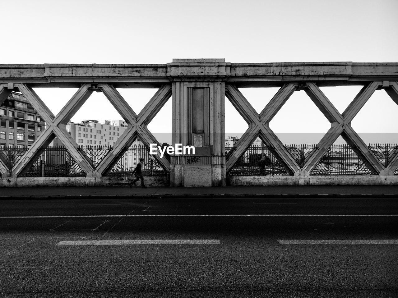 Man walking on bridge against sky