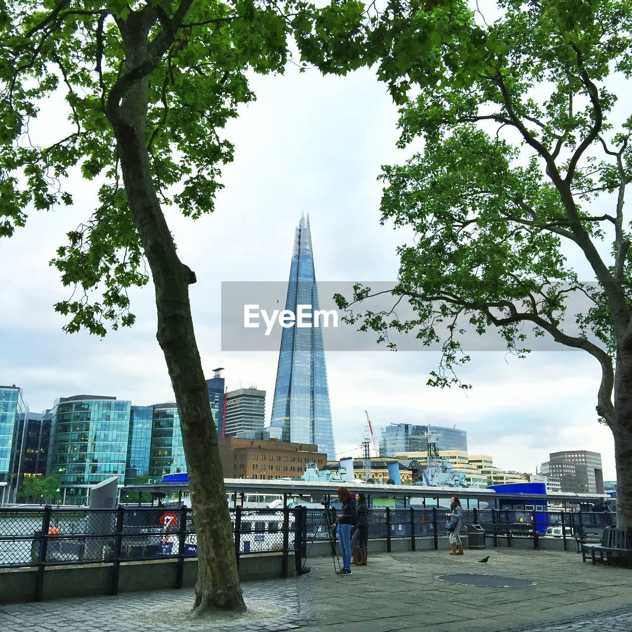 built structure, tree, architecture, tall - high, real people, building exterior, city, day, tower, skyscraper, men, sky, outdoors, leisure activity, lifestyles, women, travel destinations, full length, modern, nature, people