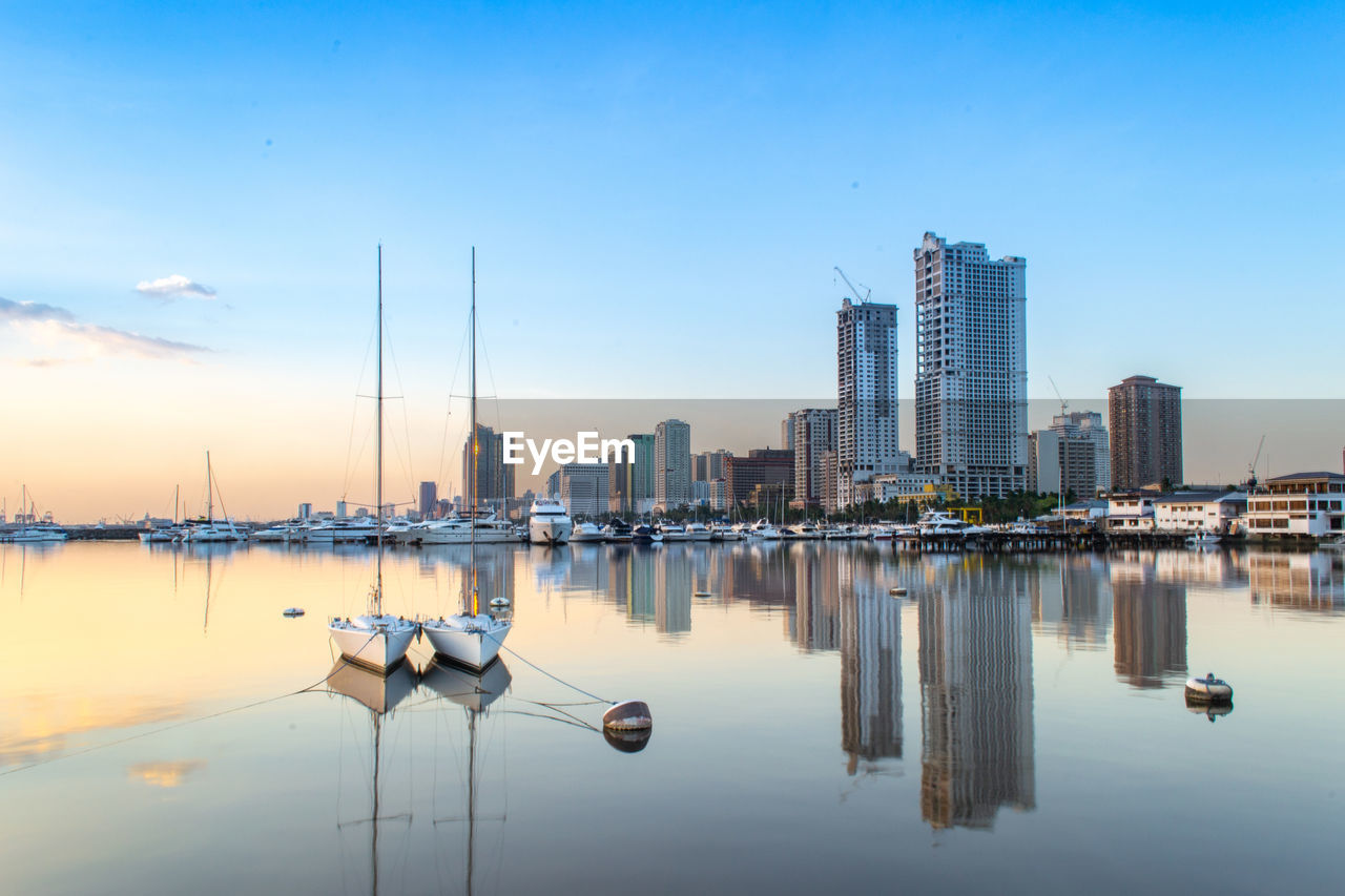 water, building exterior, sky, reflection, architecture, city, building, built structure, no people, nature, waterfront, tower, nautical vessel, office building exterior, urban skyline, skyscraper, tall - high, transportation, outdoors, cityscape, modern, sailboat, yacht, marina, financial district