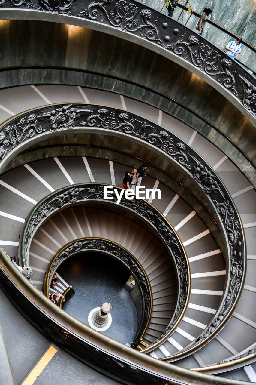 architecture, built structure, spiral, steps and staircases, spiral staircase, railing, staircase, day, high angle view, one person, indoors, directly above, design, real people, pattern, women, diminishing perspective