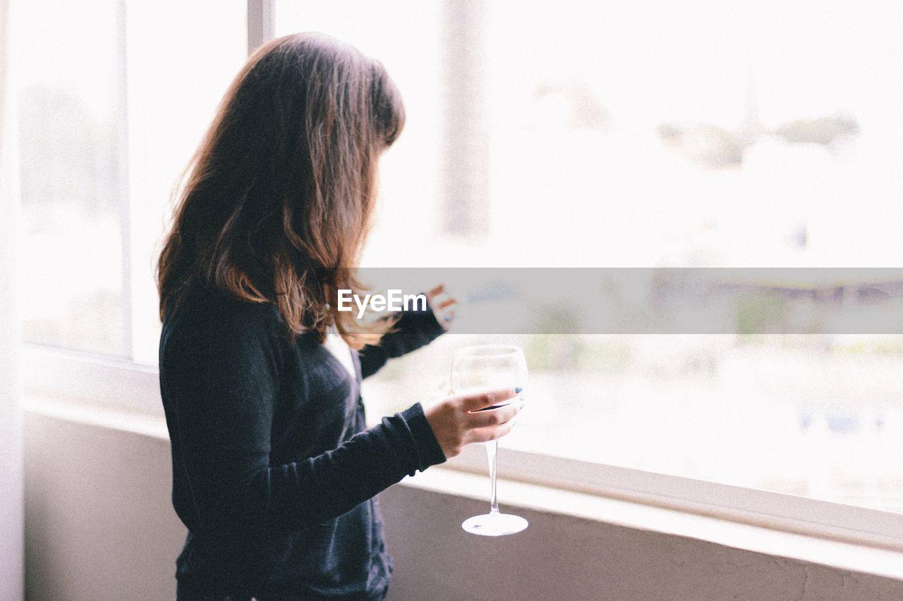 Woman Holding Wineglass By Window