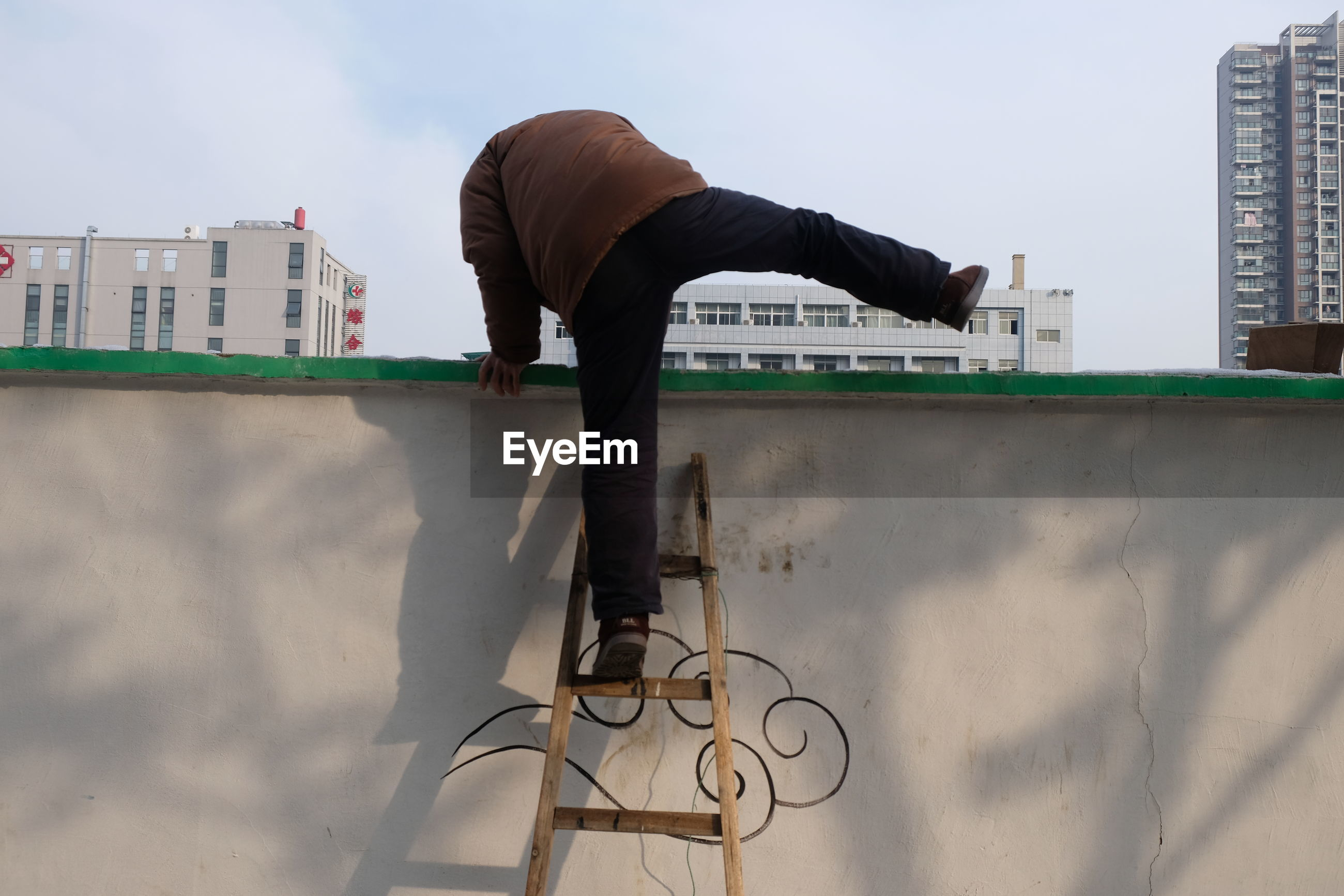 Low angle view of man climbing on wall with help of ladder