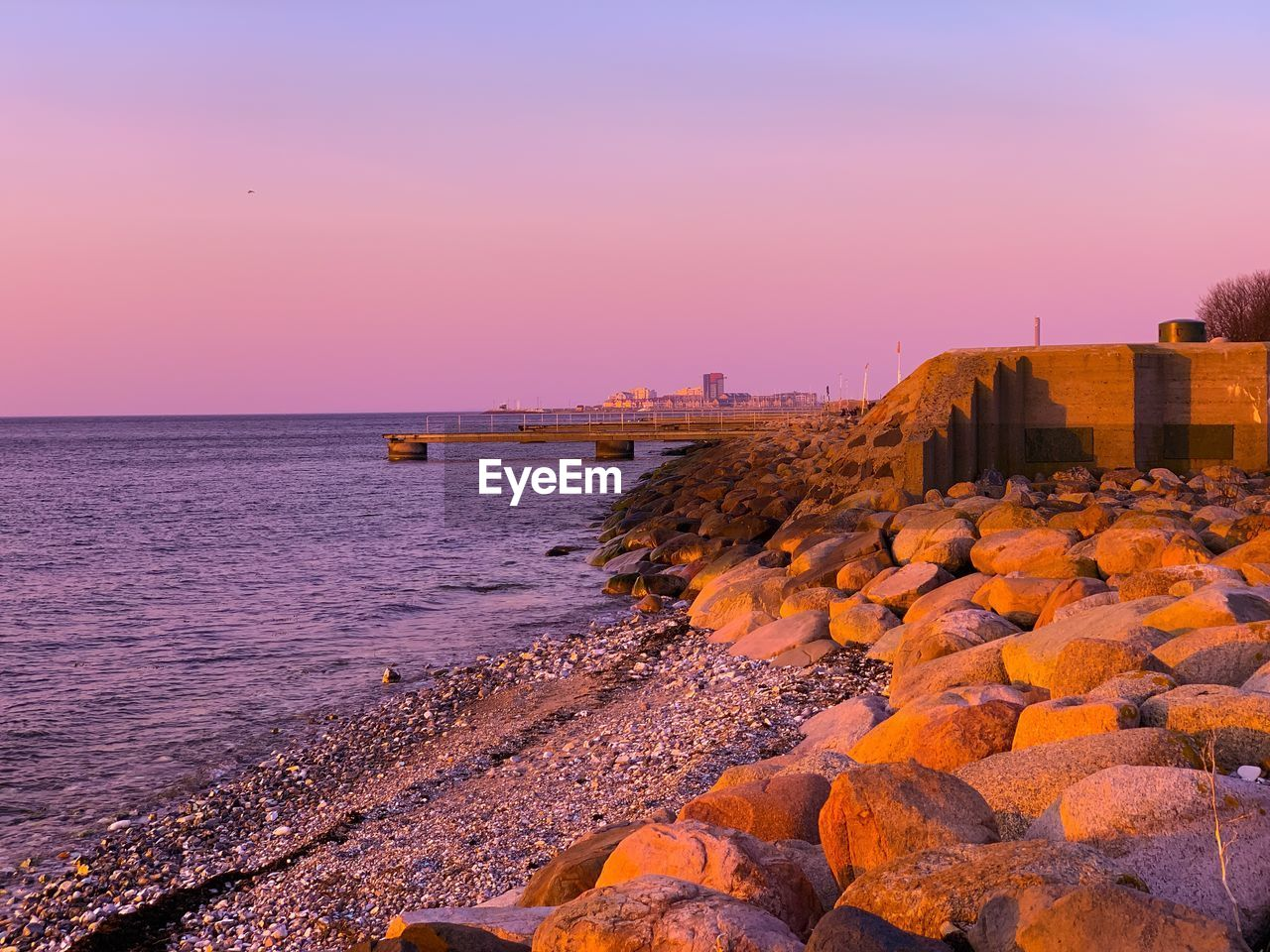 sky, water, sea, sunset, orange color, beauty in nature, nature, built structure, scenics - nature, architecture, rock, clear sky, solid, beach, no people, building exterior, rock - object, tranquility, tranquil scene, horizon over water, outdoors, groyne