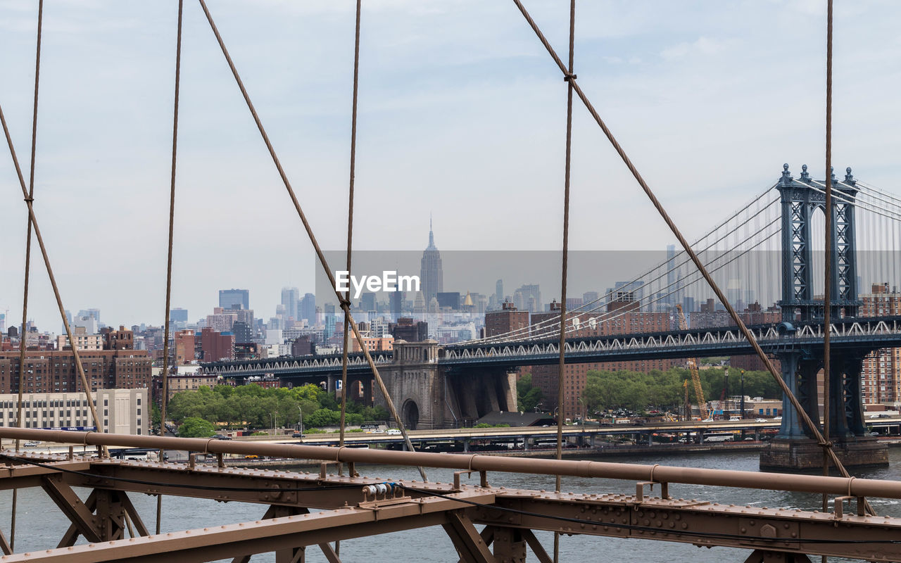 Steel Cables Of Bridge With Buildings In Backgrounds