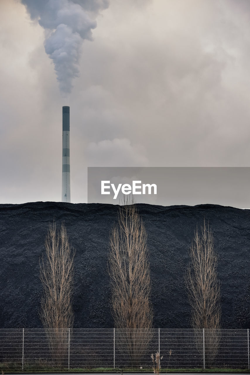 Smoke stack on field against sky