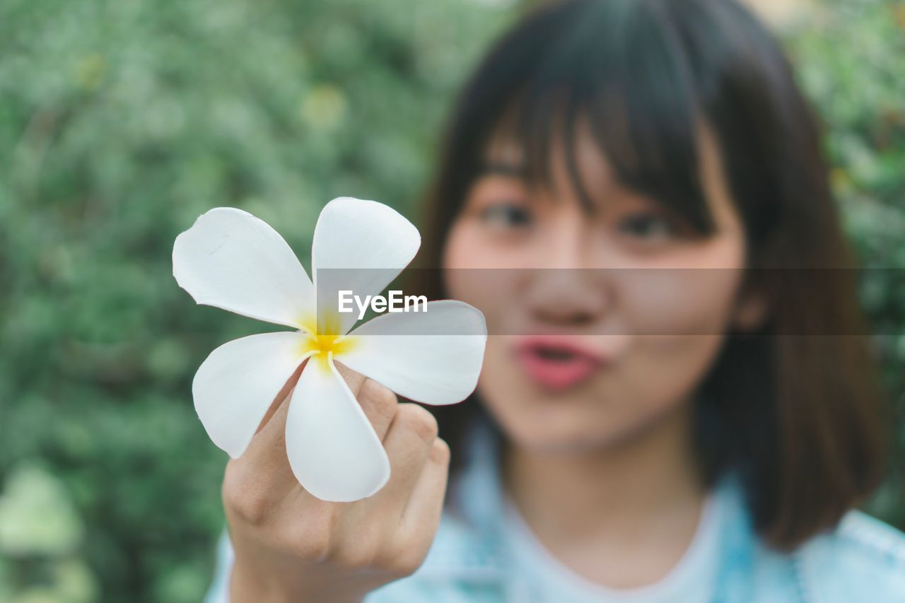 Close-up of woman holding flower in park