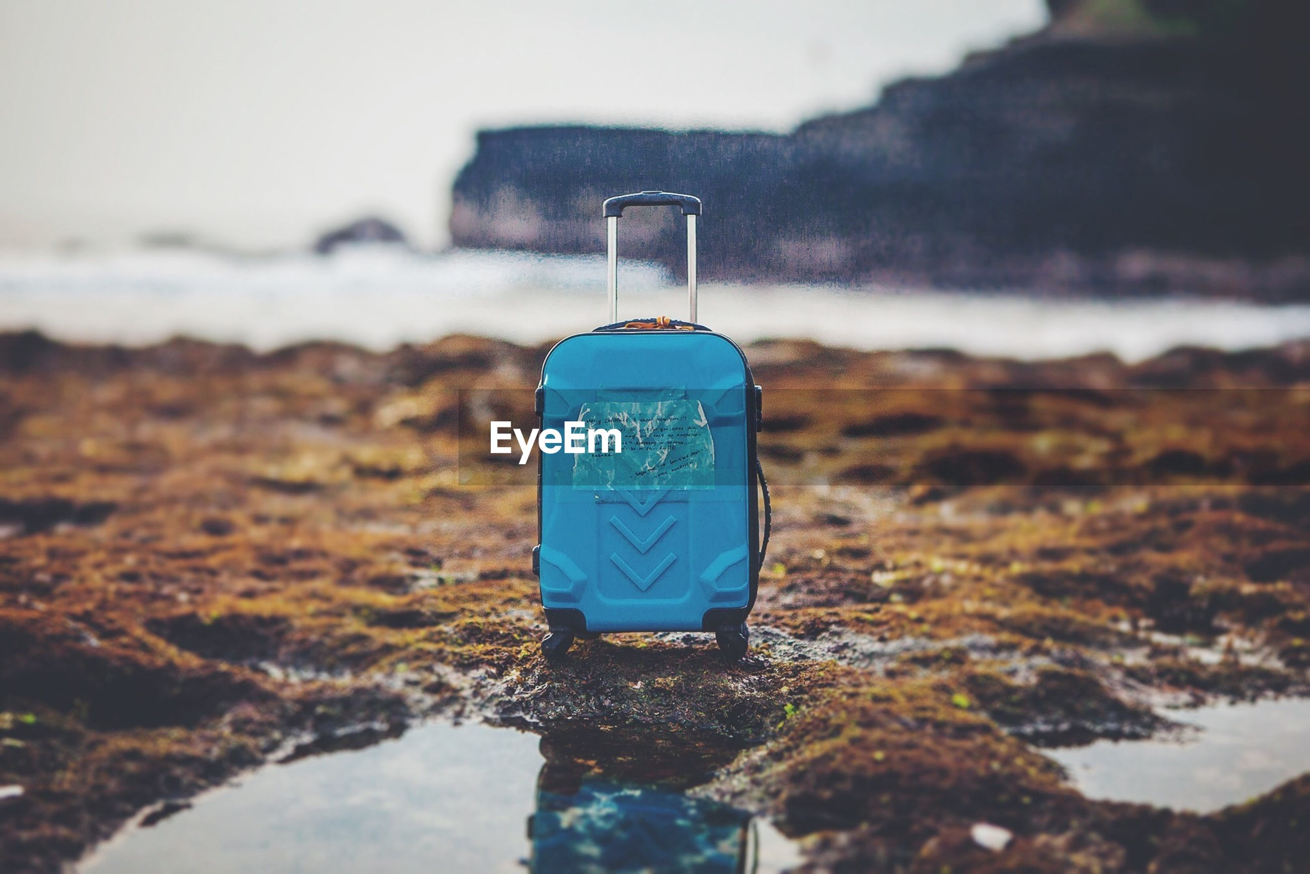 Blue luggage on field by water