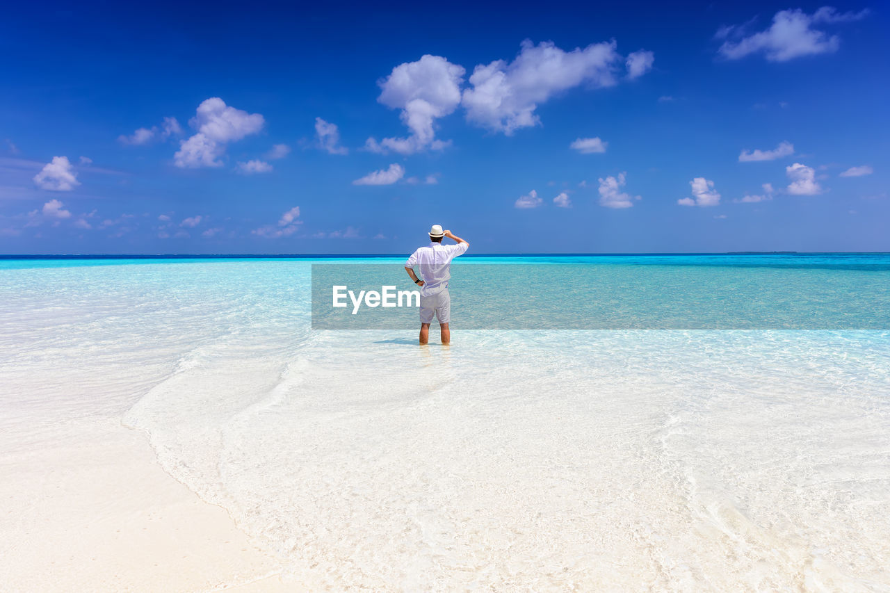Rear view of man looking at sea while standing on shore at beach against sky