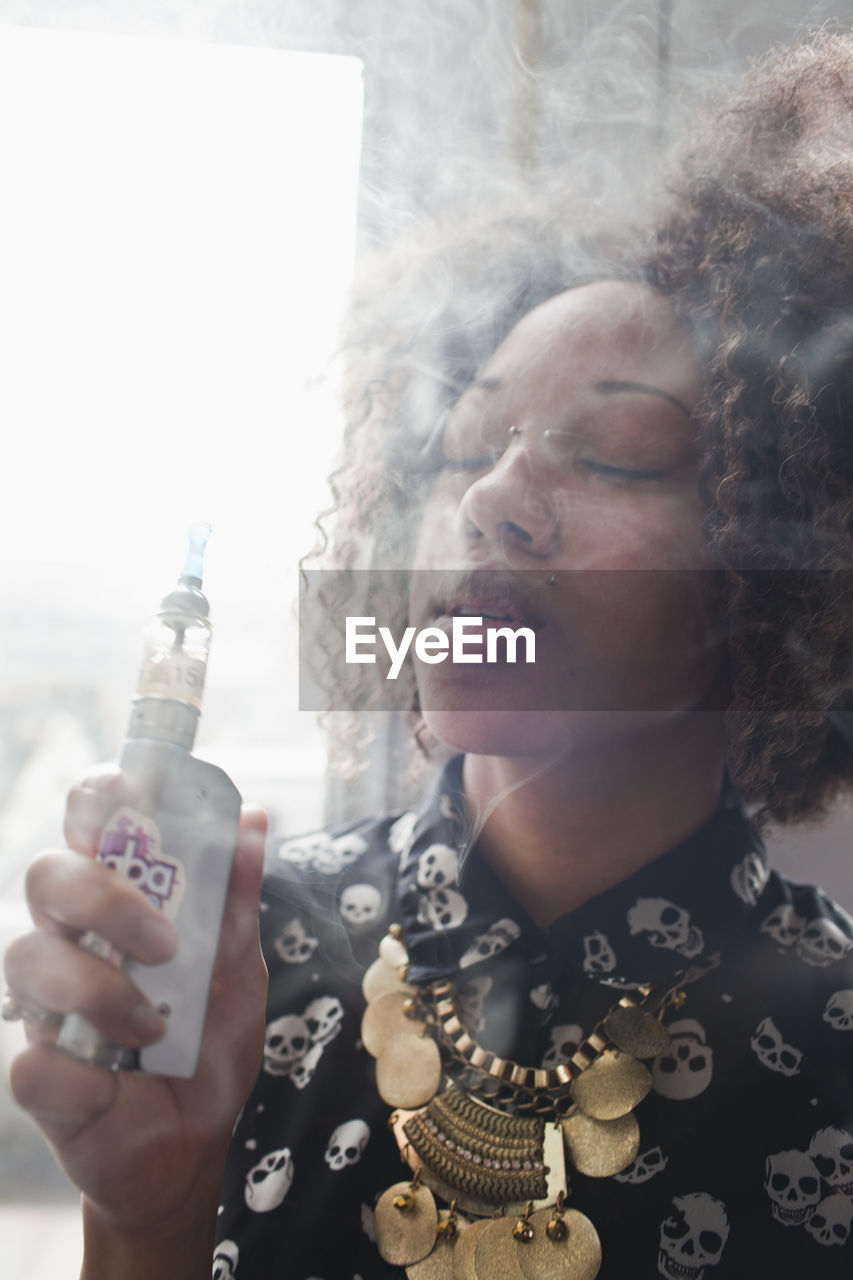 one person, real people, holding, headshot, portrait, lifestyles, adult, front view, leisure activity, smoke - physical structure, smoking issues, communication, bad habit, cigarette, women, focus on foreground, hairstyle