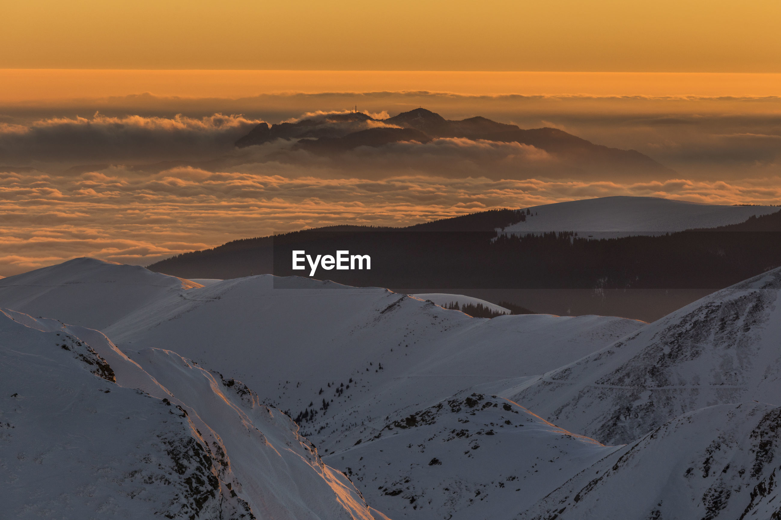 Aerial view of snowcapped mountains against sky during sunset, fagaras mountains