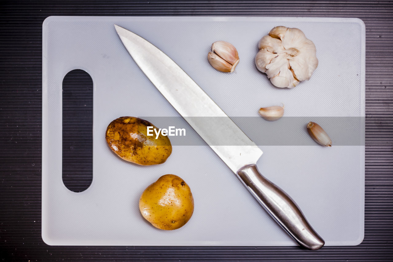 Directly above shot of knife and vegetables on cutting board