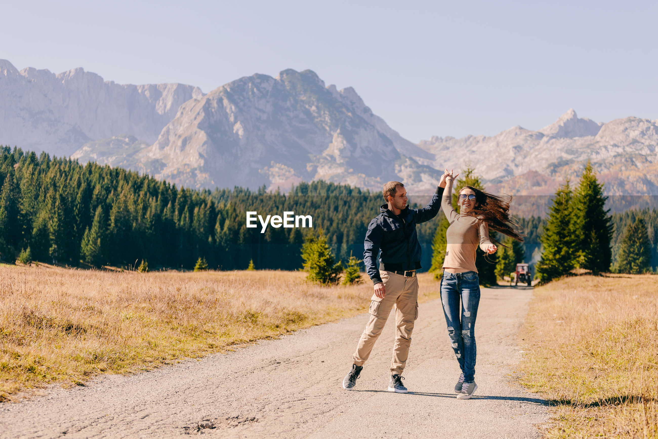 Cheerful couple standing on road against mountains