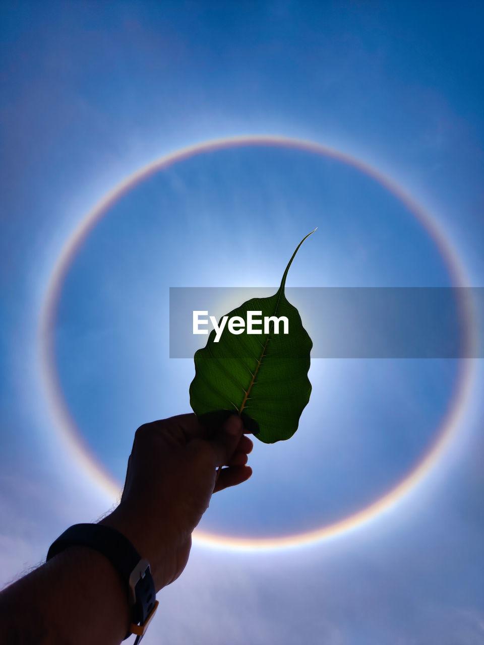 PERSON HOLDING RAINBOW AGAINST BLUE SKY