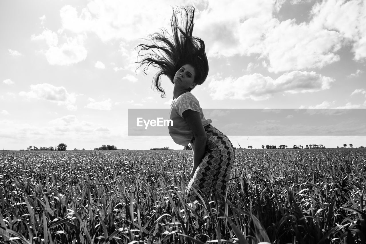 Portrait of woman tossing hair while standing amidst plants