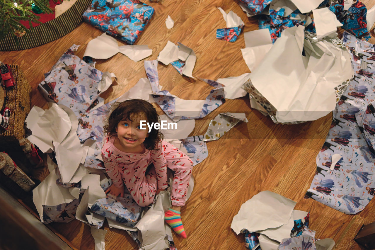High angle view portrait of girl on floor at home