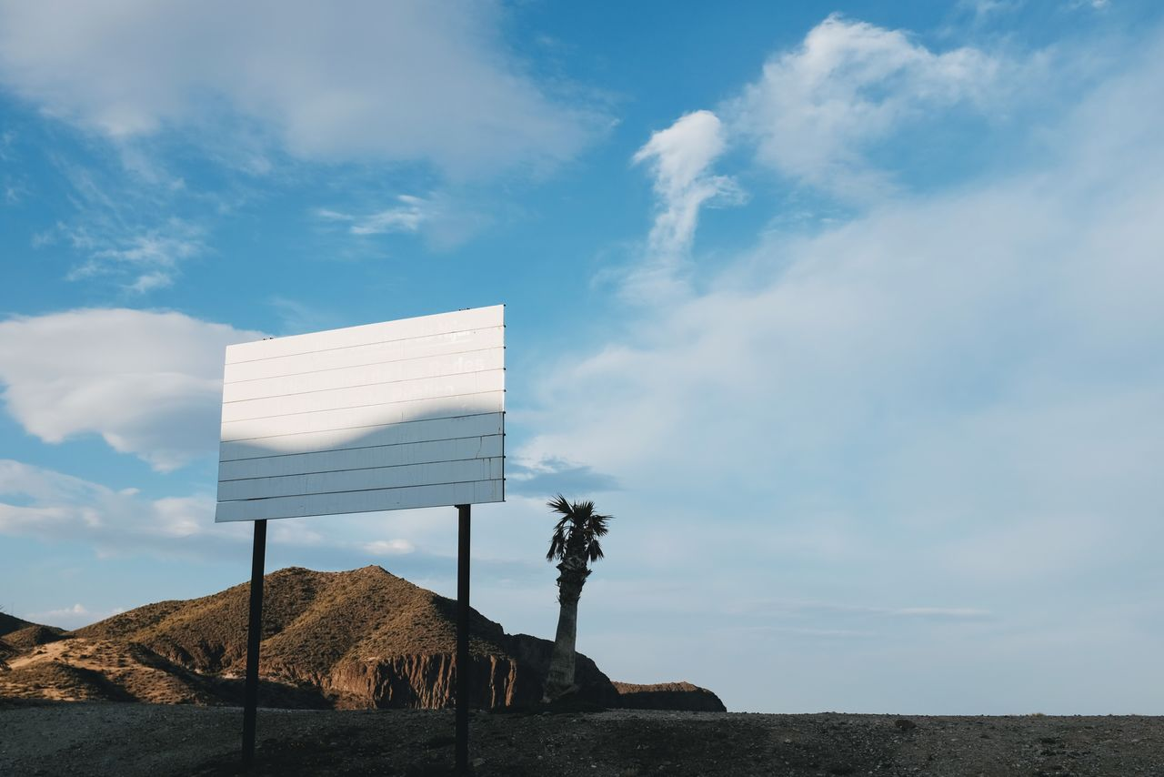 Blank Billboard On Land Against Mountain And Sky