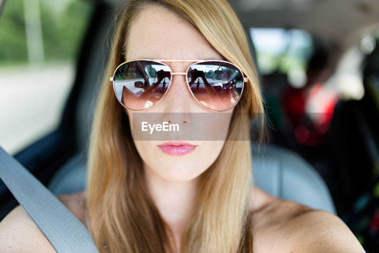 Portrait of woman wearing sunglasses while sitting in car