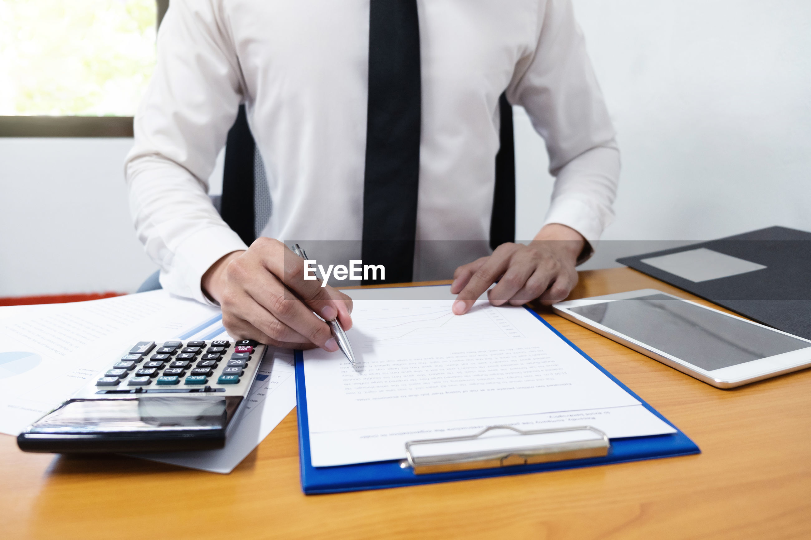 Midsection of businessman writing on clipboard on desk in office