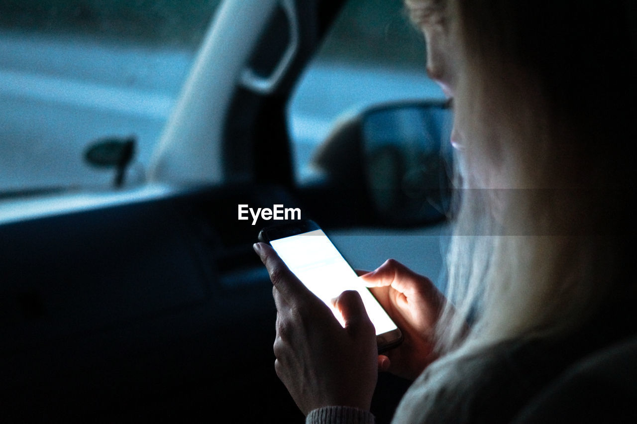 Cropped image of woman using smart phone in car