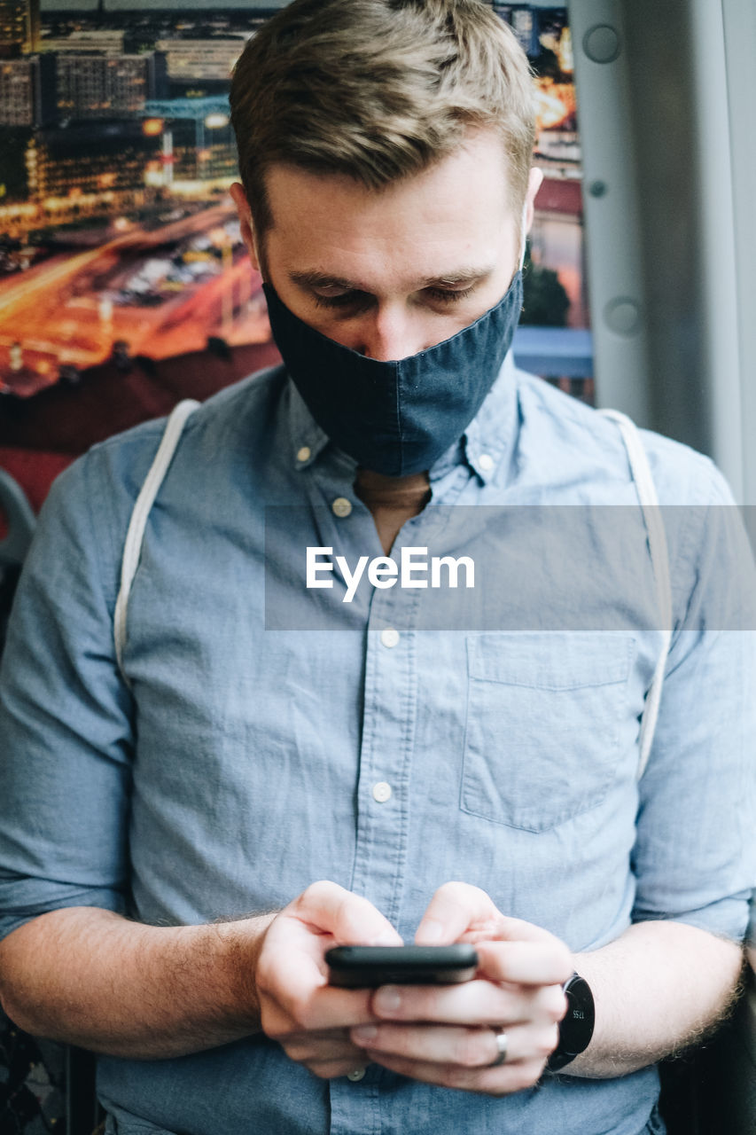 Man wearing mask using mobile phone in train