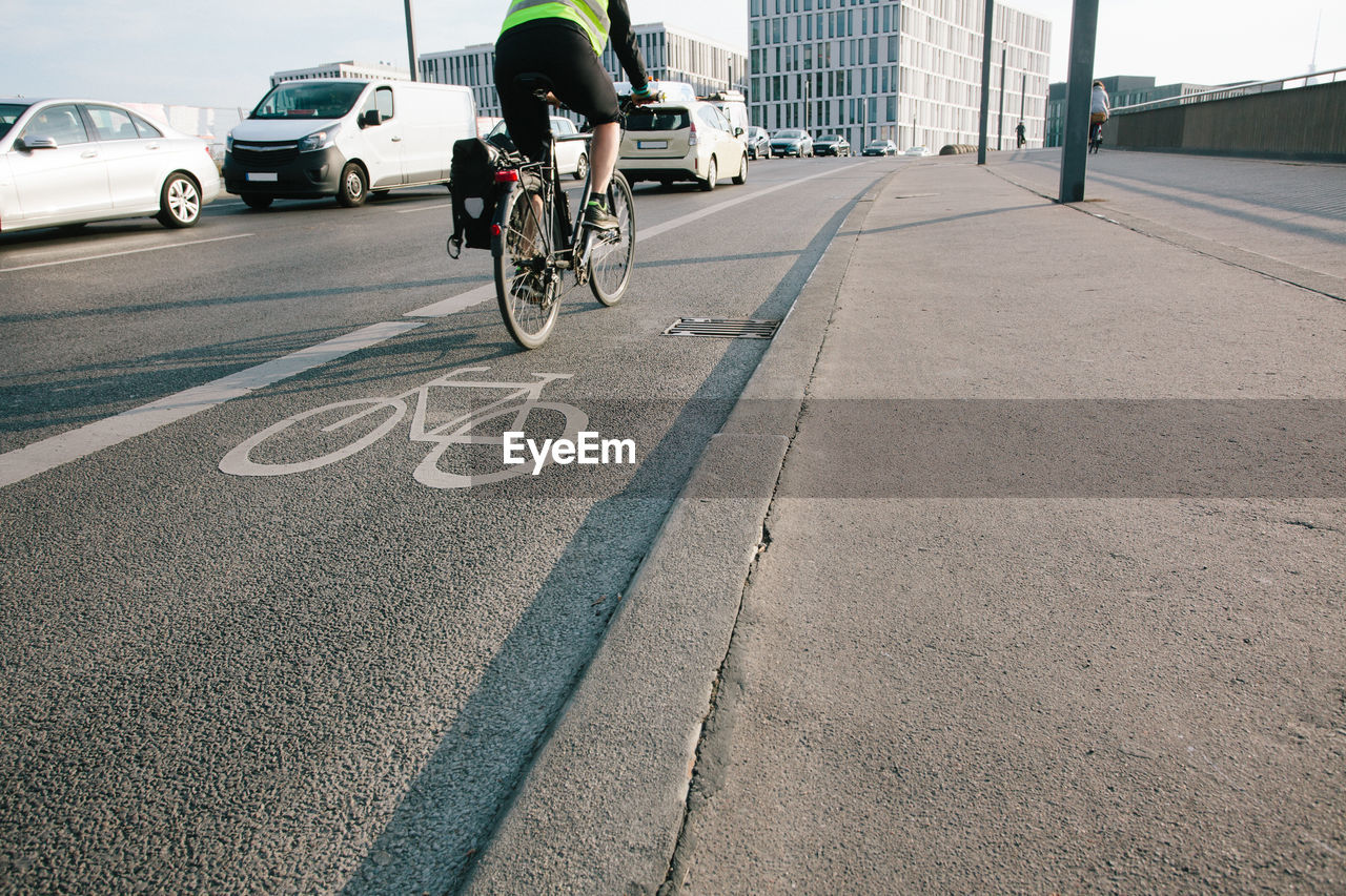 Low Section Of Man Riding Bicycle On Road In City