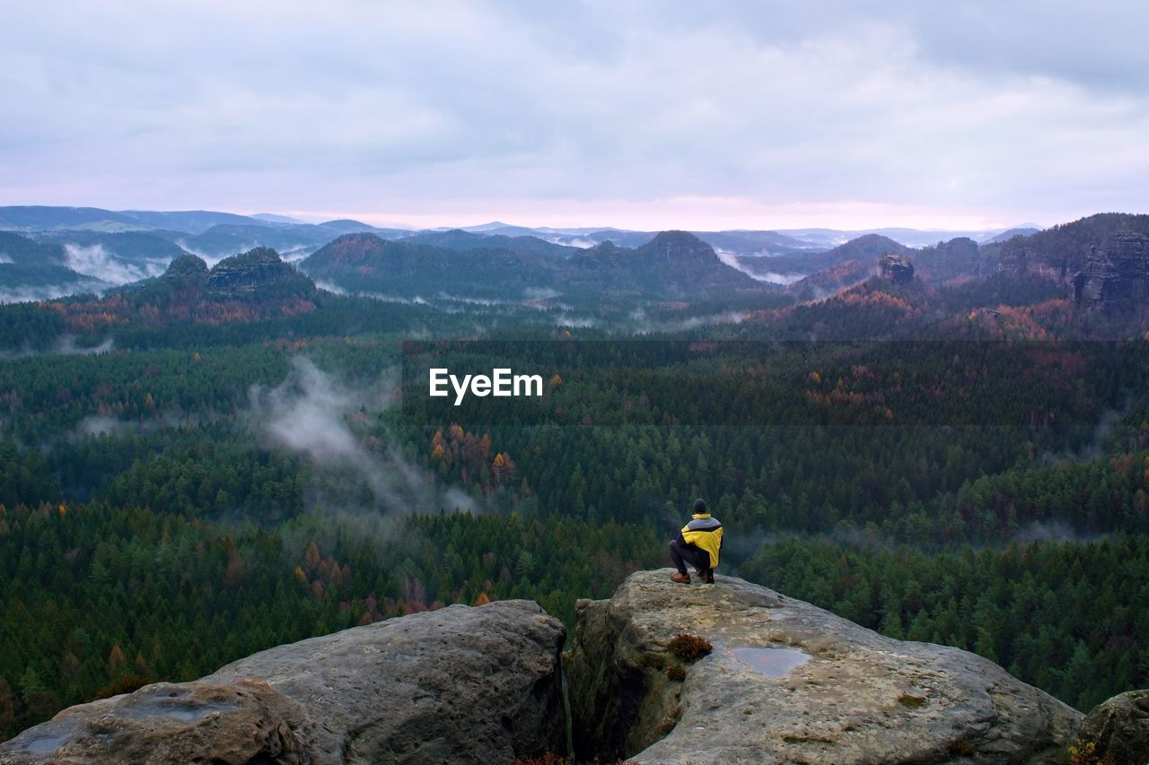 Rear view of male hiker in yellow black jacket on rocky peak while enjoying a daybreak above valley