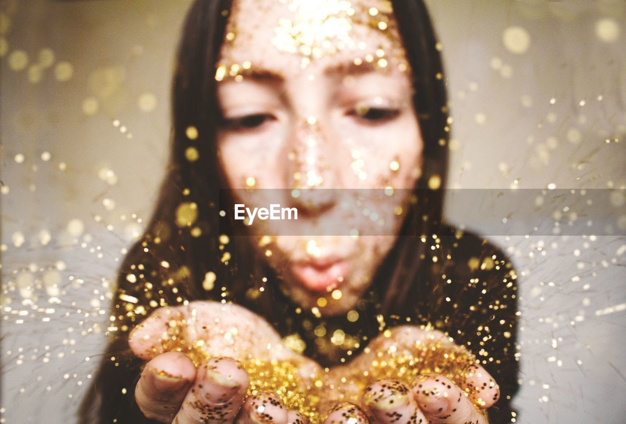 Close-Up Of Young Woman Blowing Confetti