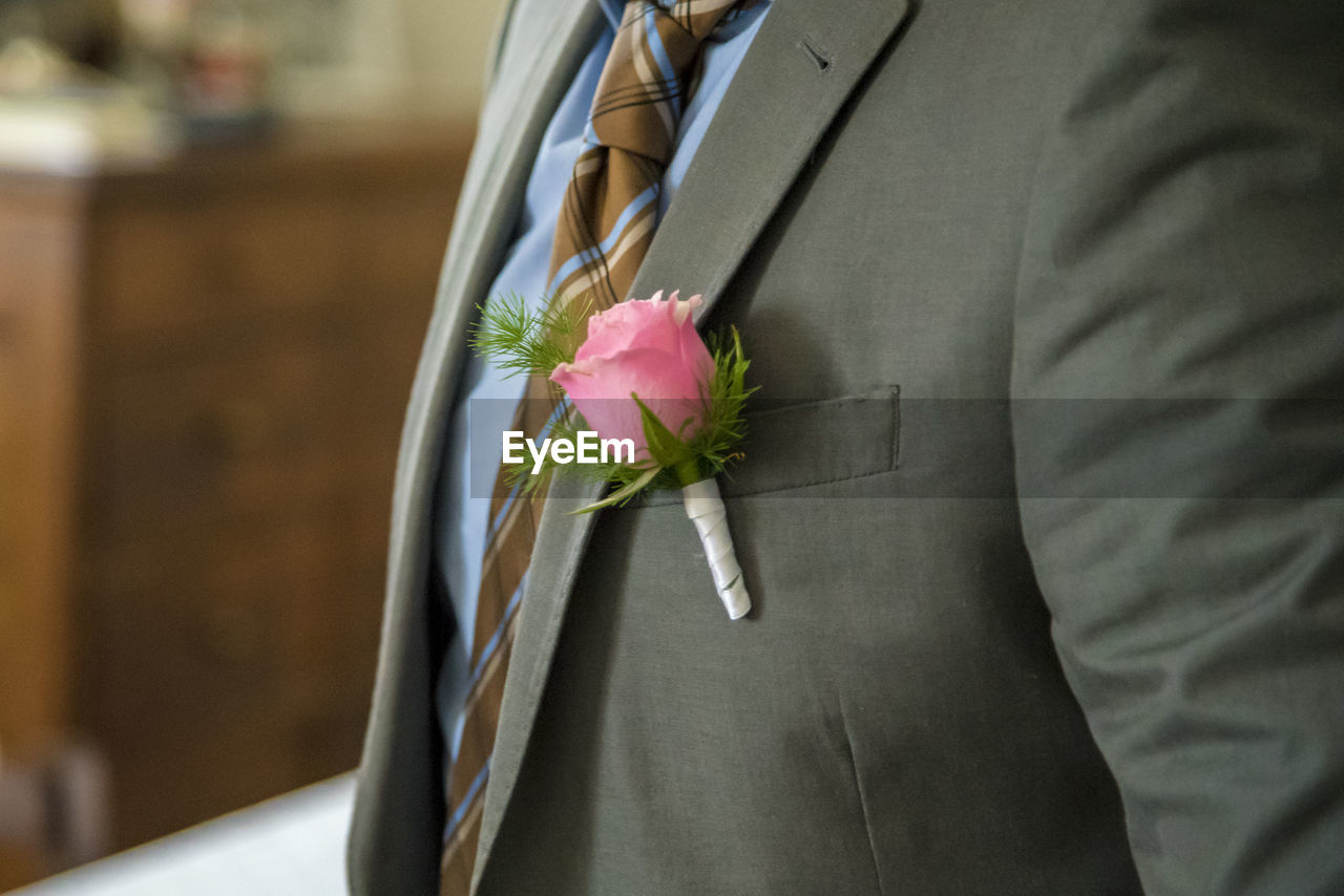midsection, flower, flowering plant, plant, holding, beauty in nature, one person, men, close-up, focus on foreground, freshness, adult, lifestyles, well-dressed, suit, pink color, nature, rose, fragility, flower arrangement, flower head, bouquet