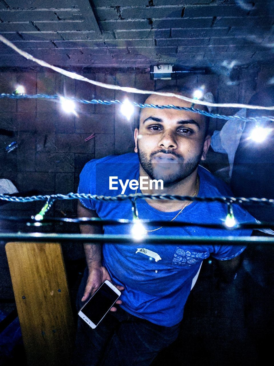 illuminated, lens flare, one person, lighting equipment, front view, real people, night, indoors, portrait, occupation, looking at camera, lifestyles, beard, welder, men, nightclub, young adult, one man only, only men, adult, people, adults only