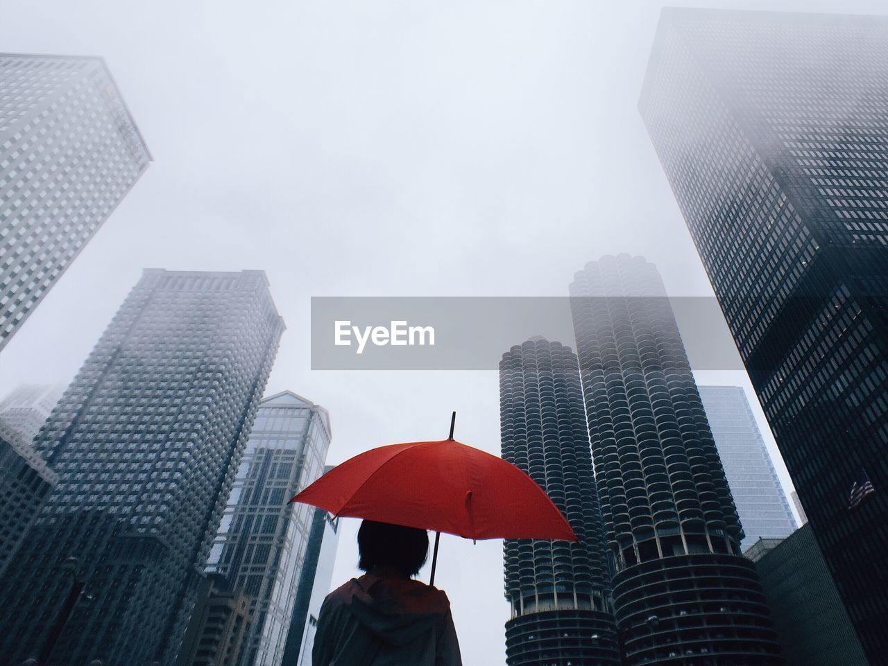Woman with red umbrella standing in front of modern office blocks