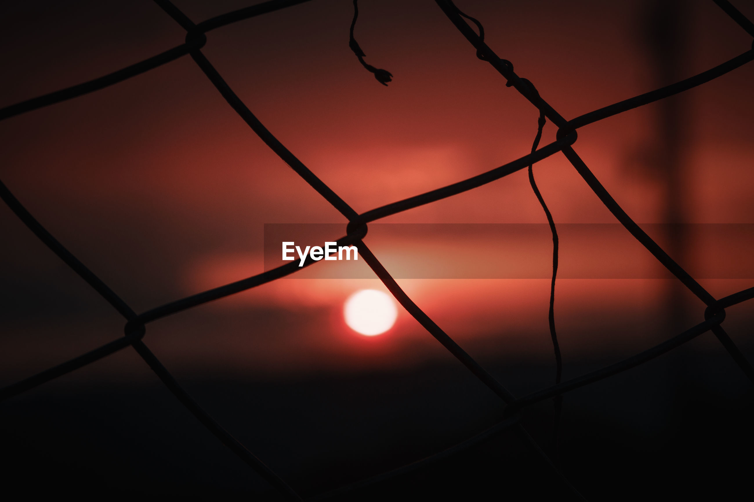 CLOSE-UP OF SILHOUETTE FENCE AGAINST ORANGE SKY