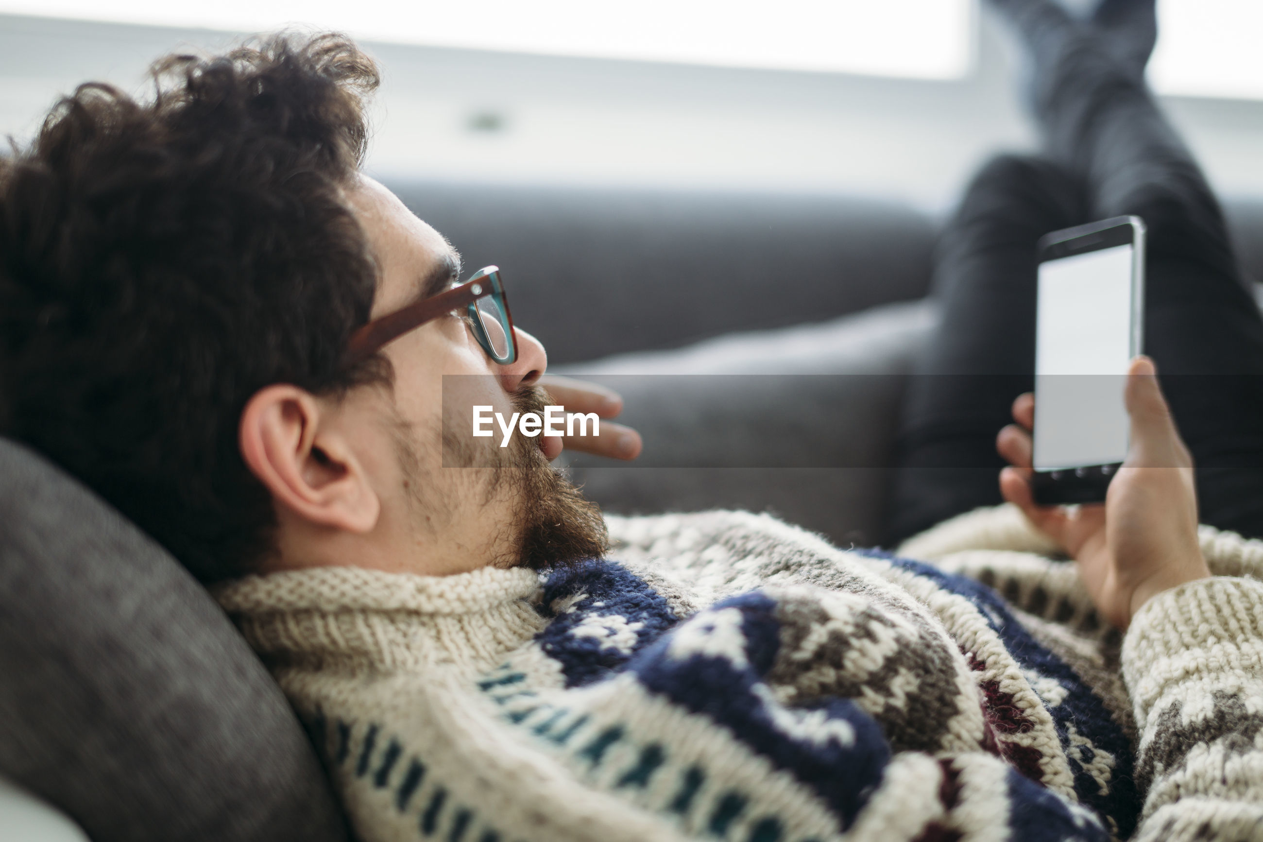 MIDSECTION OF MAN USING MOBILE PHONE IN LAPTOP