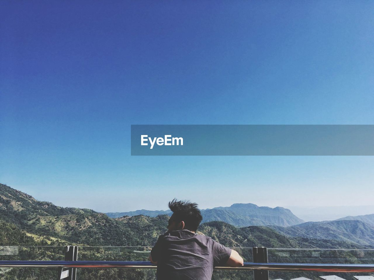 Man looking at view against clear blue sky