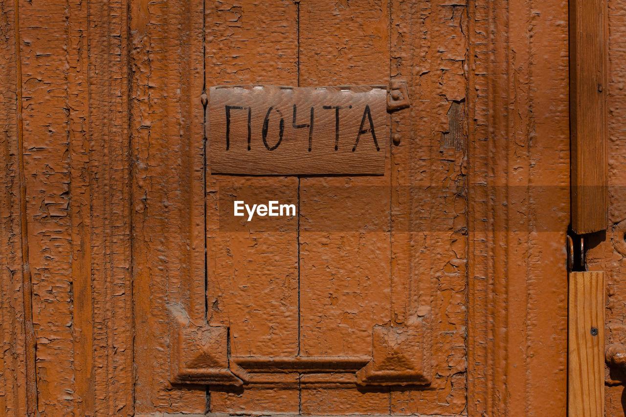 Close-Up Of Nameplate On Brown Wooden Door
