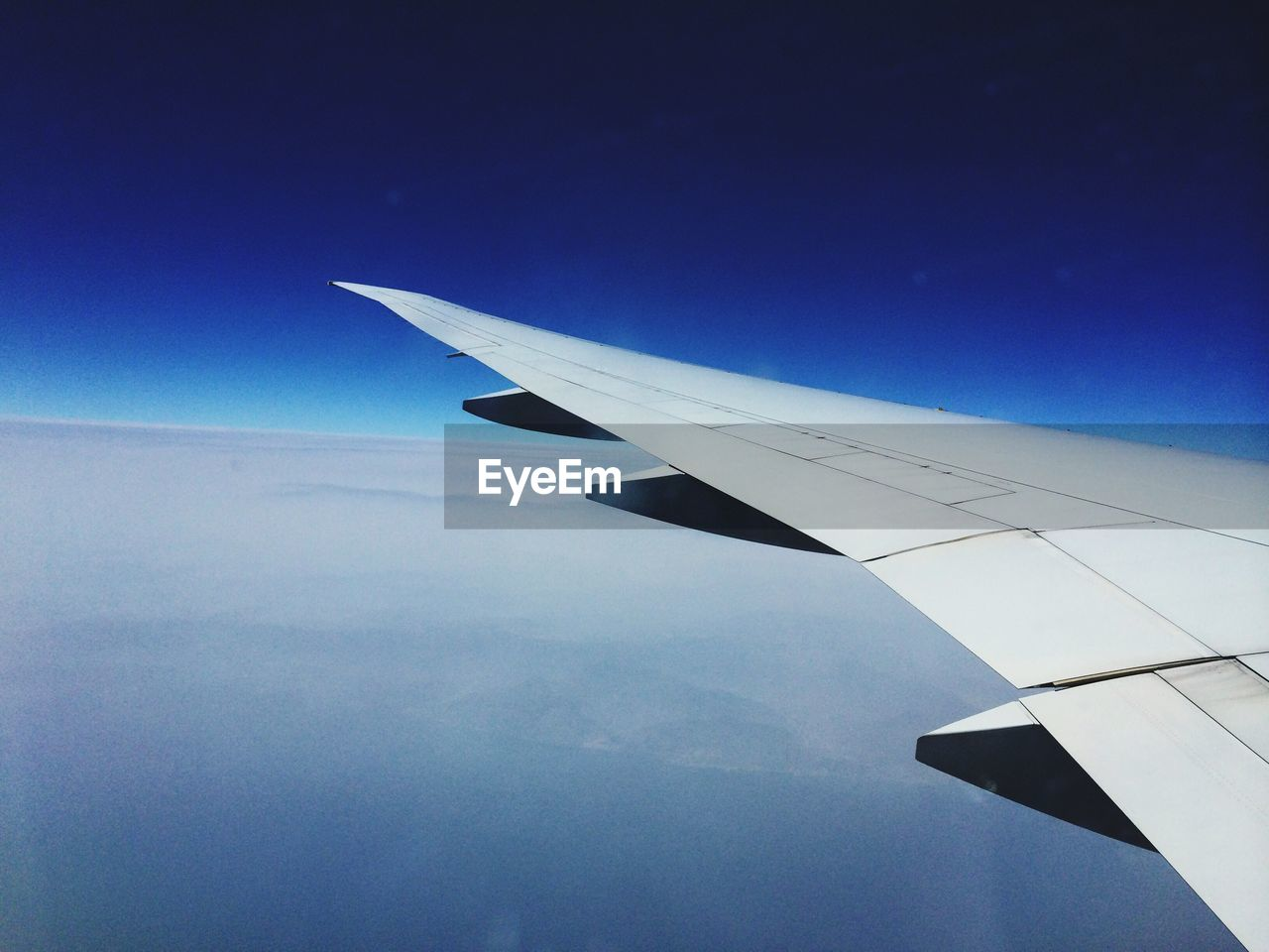Close-Up of Airplane Wing Flying Above Clouds