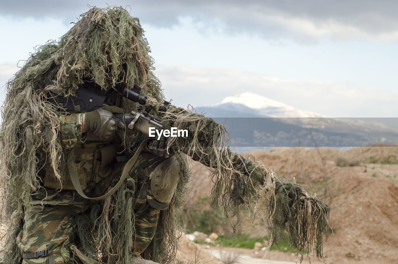 Sniper Holding Rifle Against Sky