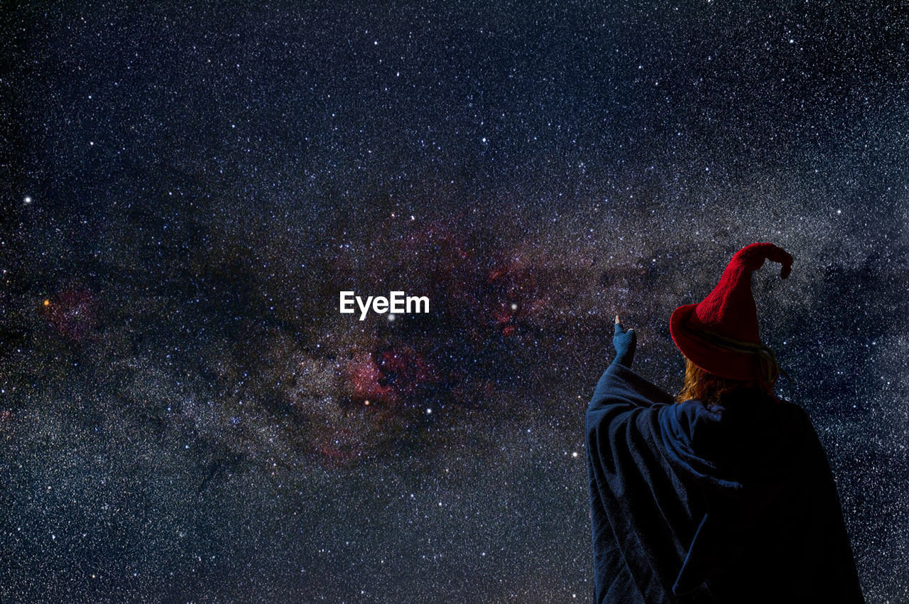 A strange woman in a red hat looks at the starry sky