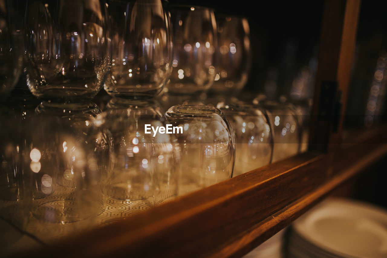 glass - material, transparent, indoors, no people, container, selective focus, still life, food and drink, close-up, shelf, glass, in a row, table, arrangement, large group of objects, side by side, restaurant, jar, order, illuminated, bar counter, crockery